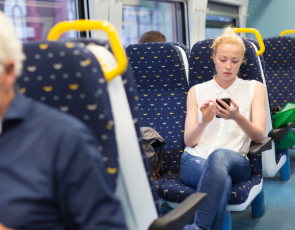 Woman looking at mobile phone on train