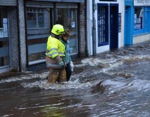 Firefighter helps woman in flooded street