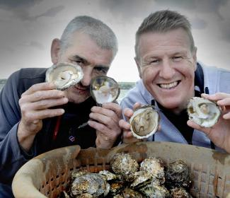 """Pictured aboard the """"Vital Spark"""", a Stranraer based fishing vessel gathering the first oyster haul of the season are Allan Jenkins (left, project manager for Stranraer Development Trust, the community organisation that runs the oyster festival) and Vital Spark captain and oyster fisherman Rab Lamont."""