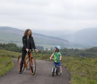 Woman and child on bikes on path