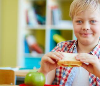 boy eating lunch at school desk