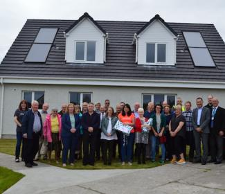 participants in house warming event standing outside the houses
