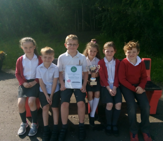 pupils from the P2/3 class accepting the cup, certificate and £50 book token